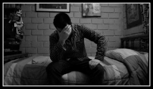 Sad man sitting on bed
